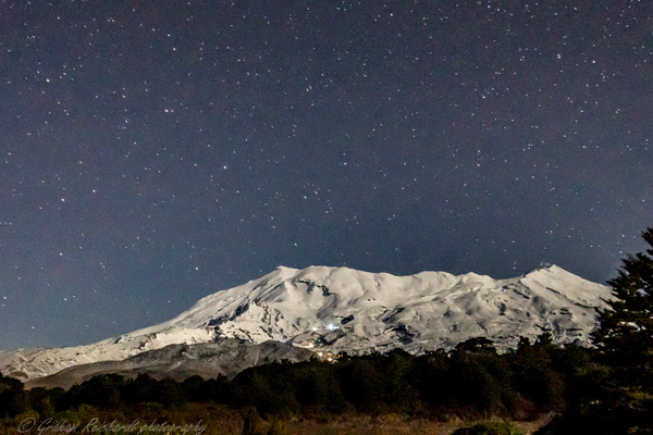 Mt Ruapehu from access Rd to Chateau with ski chalet lights on mountain and night shy behind - Night Sky - Graham Reichardt Photography