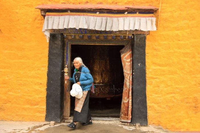 Tibetan woman leaving a large Prayer Wheels