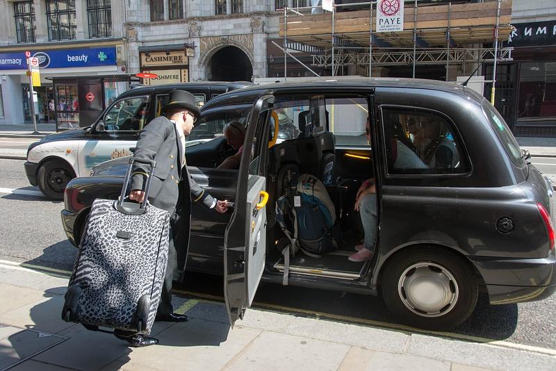 At the Strand Palace Hotel, doorman loading up black cab