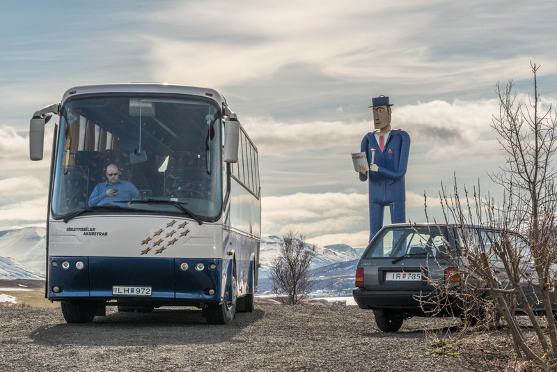 The bus driver doesn't realize how well he compliments the statue