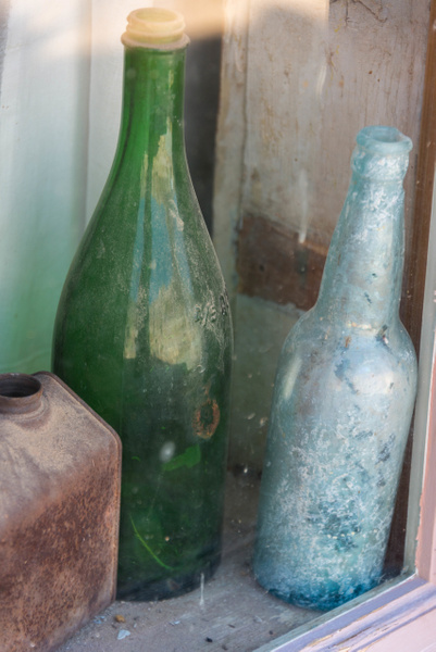 Old glass bottles not in a wall or on some art. by...