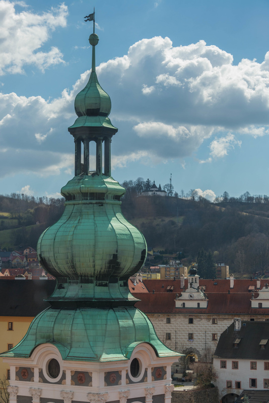 Tower of St. Jost Church to the south with křížová cesta, Stations of the Cross, on the hilltop
