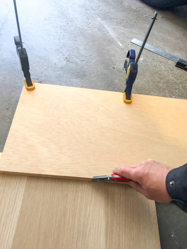 Using the header panel as a guide to cut the Askvoll back panel. Many firm passes with utility knife