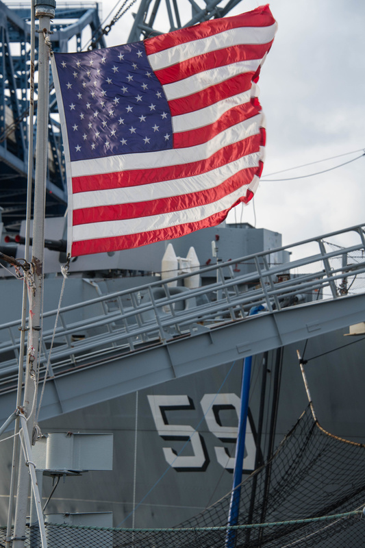 Flag in the fantail of the Joe Kennedy, looking at the stern of the USS Massachusetts.