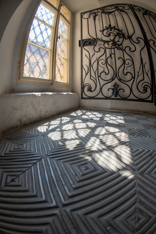 Patterns of light and shadow on the floor at the bottom of the grand staircase of the Libeň Chateau