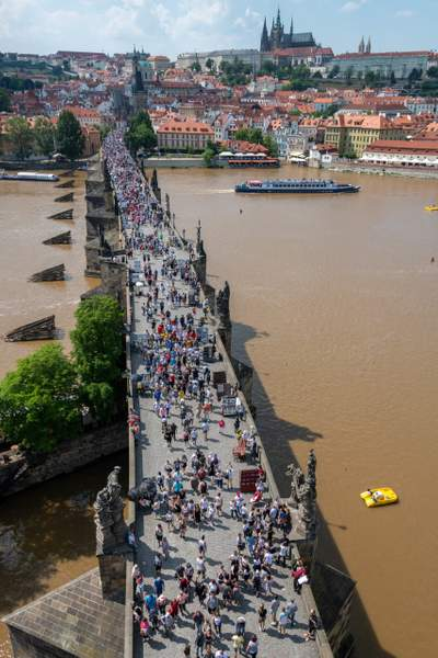 Clear afternoon light on the tourists crossing the Charles Bridge, Praha.
