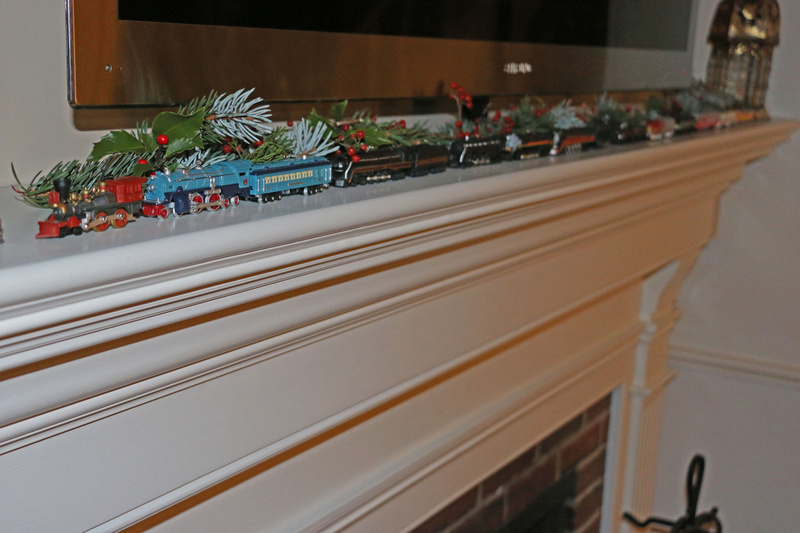 Tom's fleet of Lionel Train ornaments chug across the mantle piece.