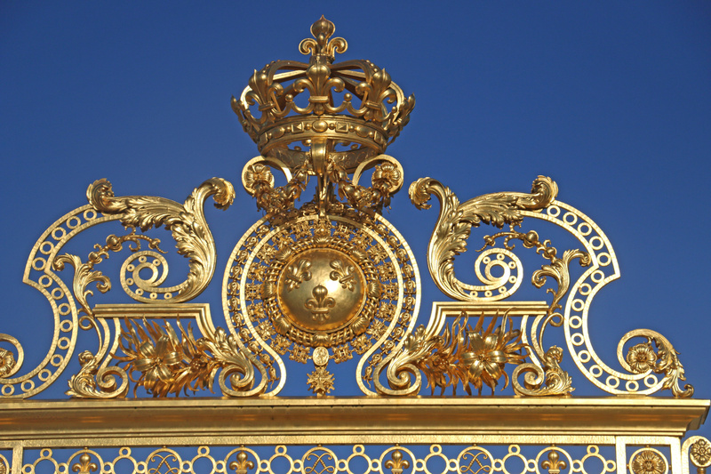 The French Royal crown and Fluer de Lis motif top the gilded fence in front of the Royal courtyard