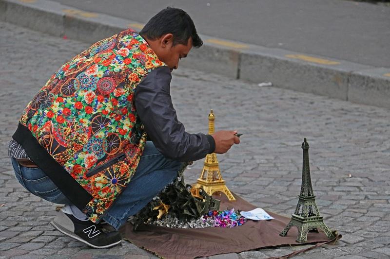 A colorful souvenir vendor sets up shop on Sacré-Cœur's plaza