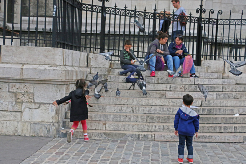 Children chasing pigeons on Sacré-Cœur's steps