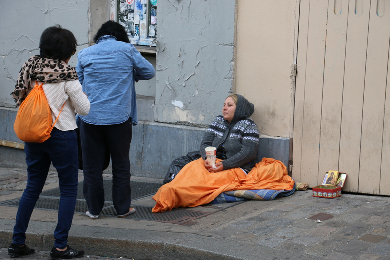 Chinese tourists assist a homeless woman