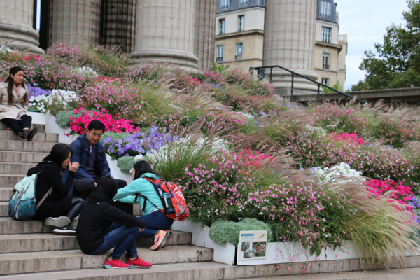 Chinese tourists resting on the steps of La Madeleine