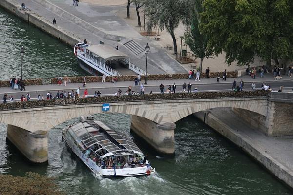 A Seine River cruiser slips beneath the The Pont de l'Archevêché (Archbishop's Bridge)