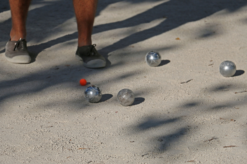 The game of Pétanque. The object is get closest to the red  cochonnet (