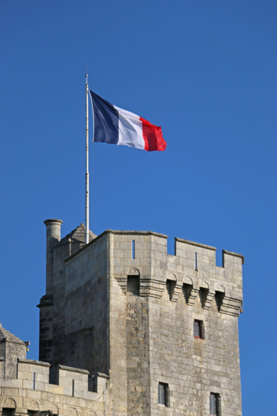The French tricolor snaps over St Nicholas Tower