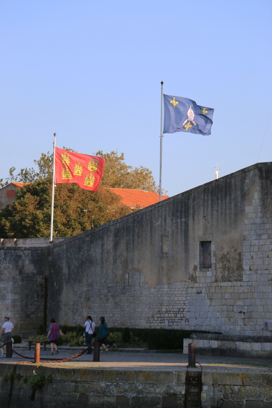 The flags of Heirs-Brouage and Saintonge flutter over a bastion