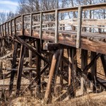 2018 An old wooden vehicle trestle over a rail line closed off to vehicle traffic.