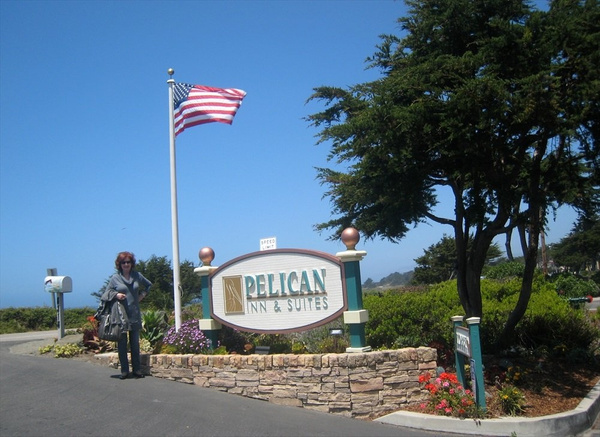 Kitty stands in front of Pelican Inn sign in Cambria telephoto by markpw2