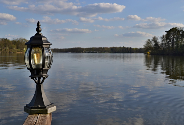 Lamp on a wooden railing over a water surface of a lake
