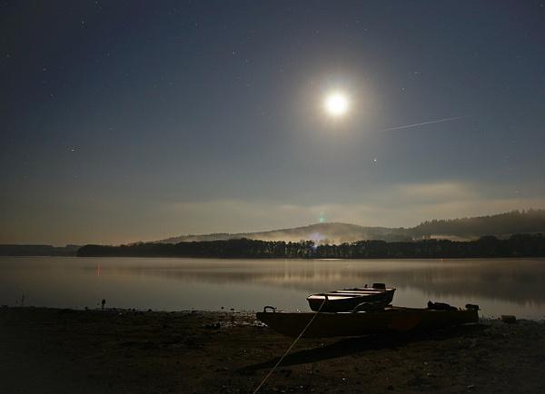 Shining moon and stars over a lake at night.