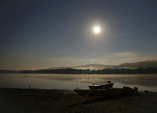 Shining moon and stars over a lake at night.