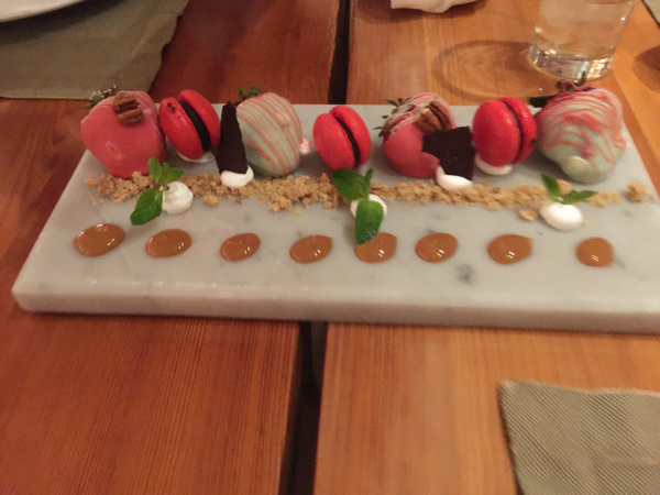 Macaroons and chocolate covered strawberries by...